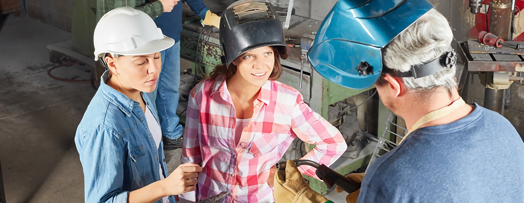two female welders learning about metal