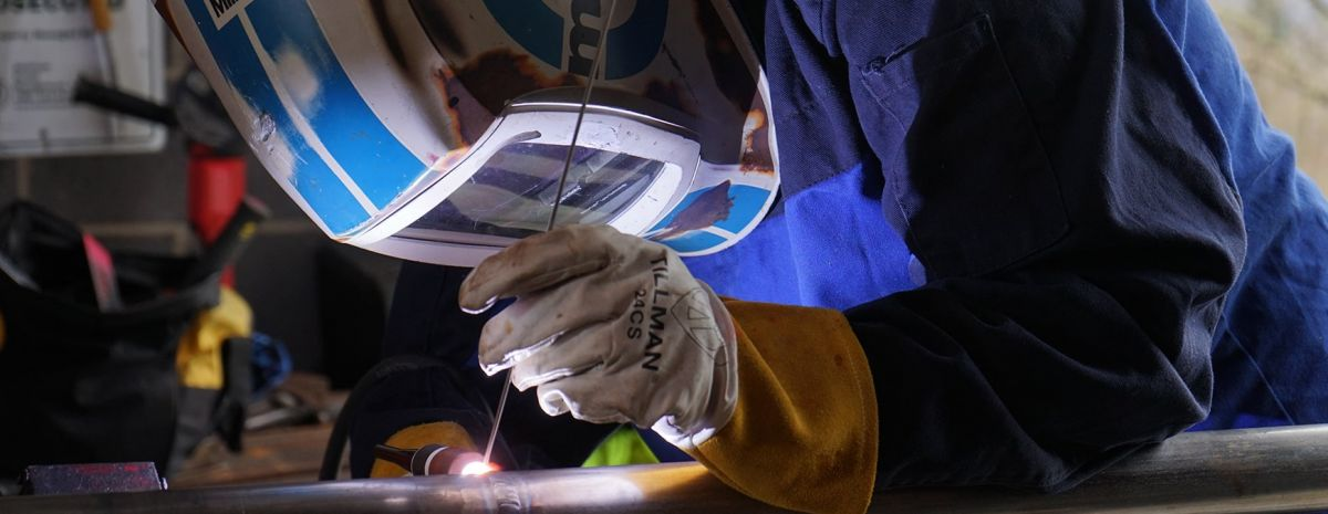 female student learning to weld