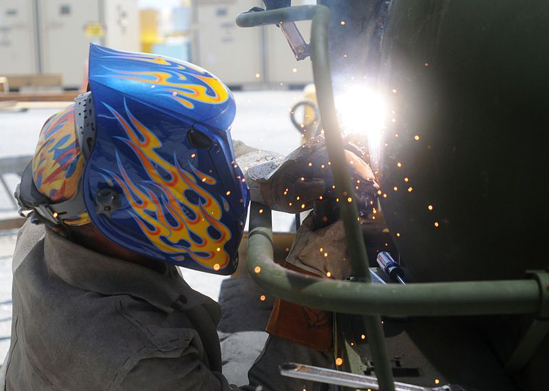 female welder with custom helmet