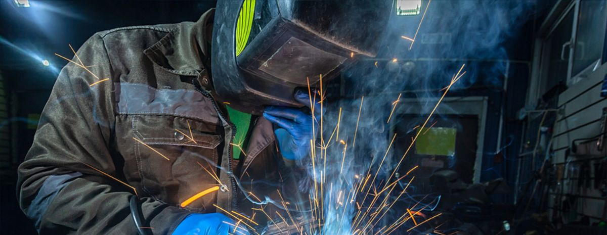 professional welder with sparks hitting helmet