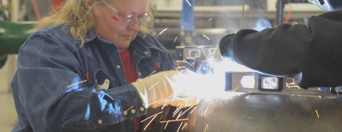 student grinds pipe in pipefitting course