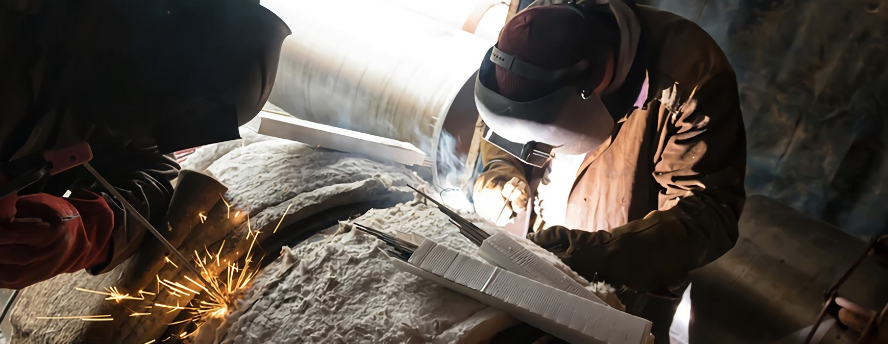 two welders pre heating pipe welding