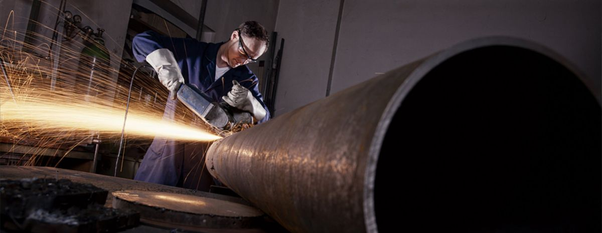 welder cutting a steel pipe