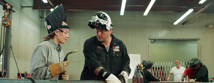 woman learning how to weld